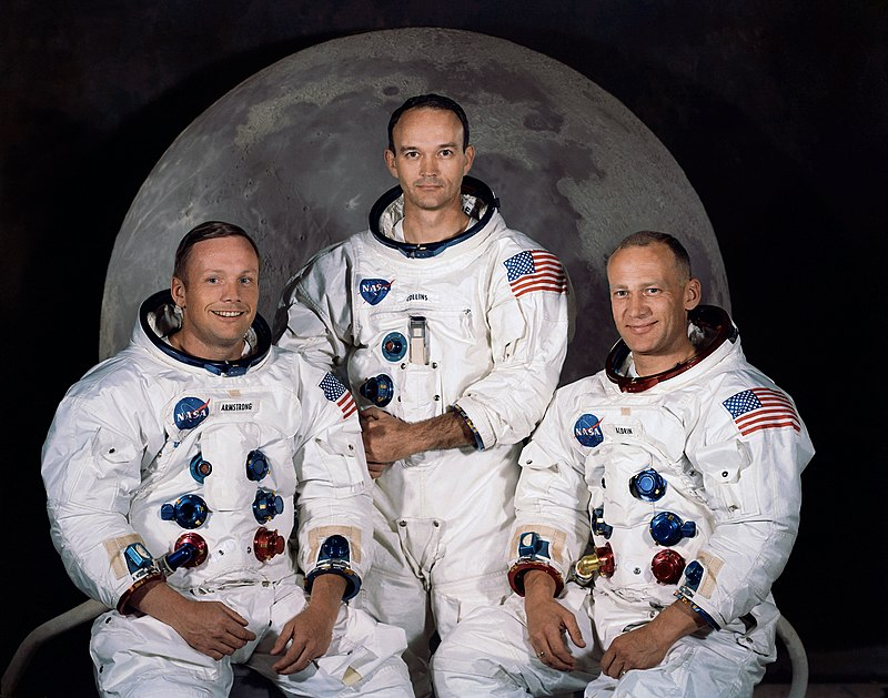 Three astronauts in spacesuits without helmets sitting in front of a large photo of the Moon. - Man on Moon, 50th anniversary of Apollo 11 spaceflight